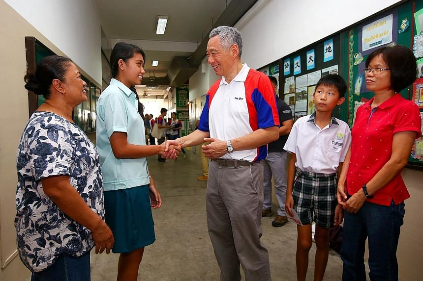 Prime Minister Lee Hsien Loong congratulating Edusave Merit Bursary award recipient Rizmawati Abdul Rasiap, seen with her mother Rosnah Atan. Beside him are fellow recipient Goh Yeow Kun and his mother, Madam Lin Xiuhua.