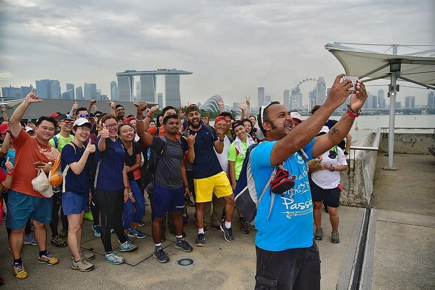 Mr Vijay Kumar taking a wefie of some of the people attempting the 100km walk around the island of Singapore. The group had set off in high spirits from Raffles Place and will walk counter-clockwise round Singapore. They aim to return to Raffles Plac