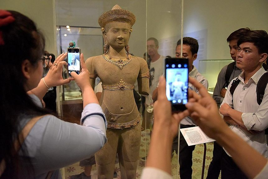 Students taking photos of a set of Angkor-era gold jewellery at the National Museum in Phnom Penh last Thursday. The jewellery was part of a set of ancient Angkorian gold which Britain returned to Cambodia last week, decades after the precious pieces
