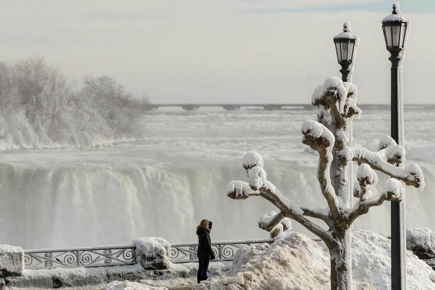 Tourists look out past the frozen railings at the Horseshoe Falls in Niagara Falls, Ontario, on Jan 3, 2018.