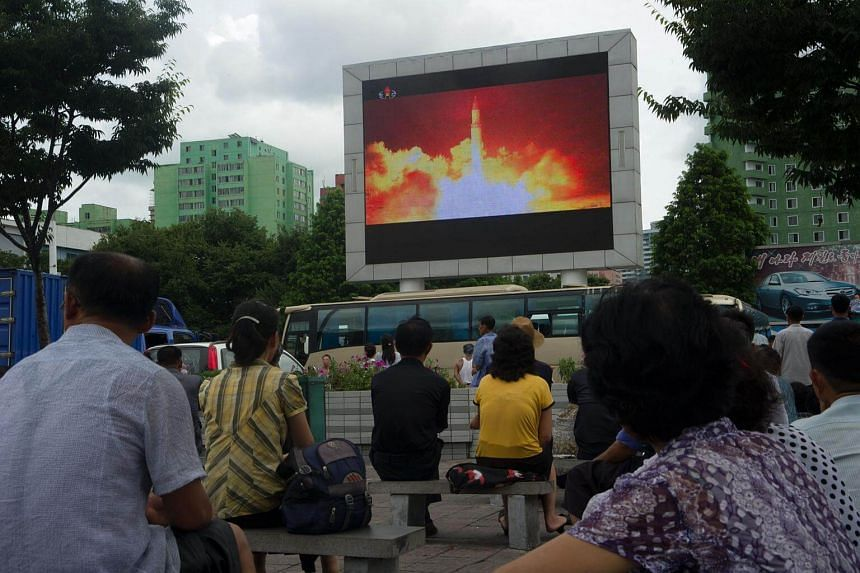 People watch as coverage of an ICBM missile test is displayed on a screen in a public square in Pyongyang, North Korea on July 29, 2017.