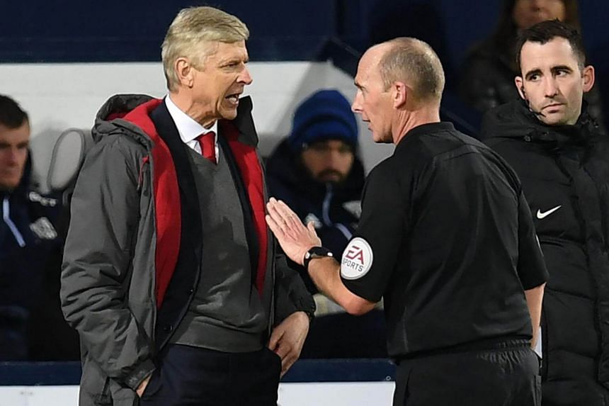 Arsenal's manager Arsene Wenger (left) has words with English referee Mike Dean during the English Premier League football match between West Bromwich Albion and Arsenal at The Hawthorns stadium in West Bromwich, on Dec 31, 2017.