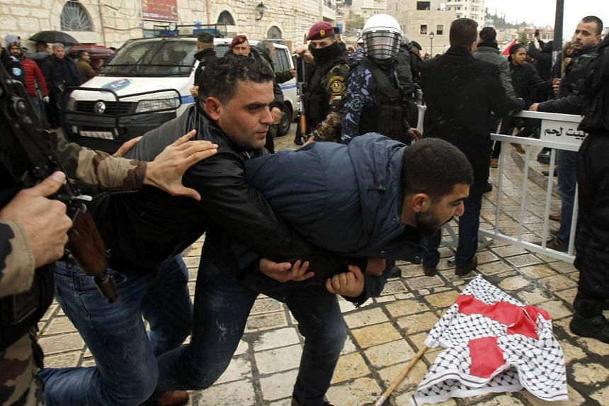 Palestinian policemen scuffle with protesters upon the arrival of the Patriarch's convoy.