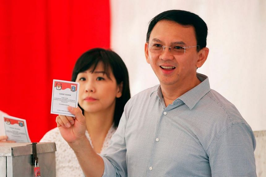 Basuki Tjahaja Purnama, popularly known as Ahok, stands alongside his wife Veronica Tan at a polling station in Jakarta on April 19, 2017.