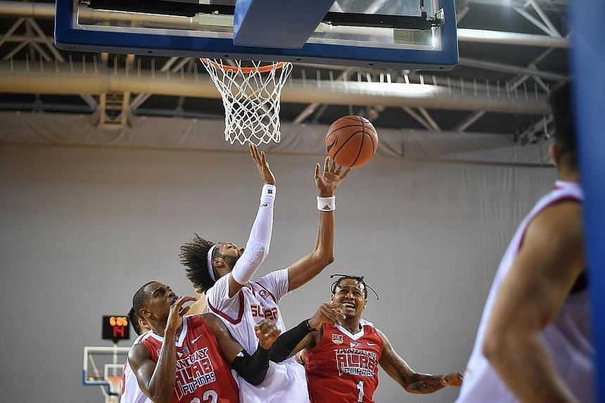 New Singapore Slingers import Christien Charles (in white) going up for a rebound with Alab Pilipinas' Justin Brownlee and Bobby Parks Jr (No. 1) at the OCBC Arena yesterday. The Slingers lost 80-89 in overtime but can make amends as both sides play