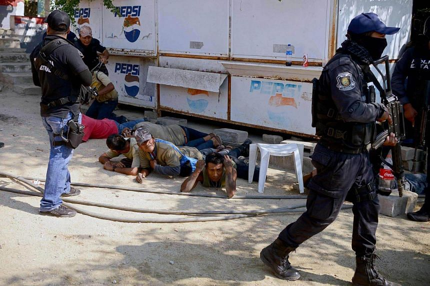 Guerrero policemen arresting a member of the Regional Coordinator of Community Authorities (CRAC) after a series of clashes at La Concepcion in Guerrero, Mexico, on Jan 7, 2018.