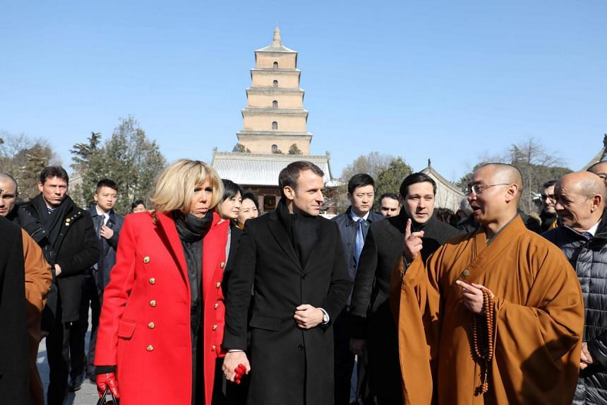 French President Emmanuel Macron (centre) and his wife Brigitte Macron listen to a priest during a visit to the Big Wild Goose Pagoda in the northern Chinese city of Xian on Jan 8, 2018.