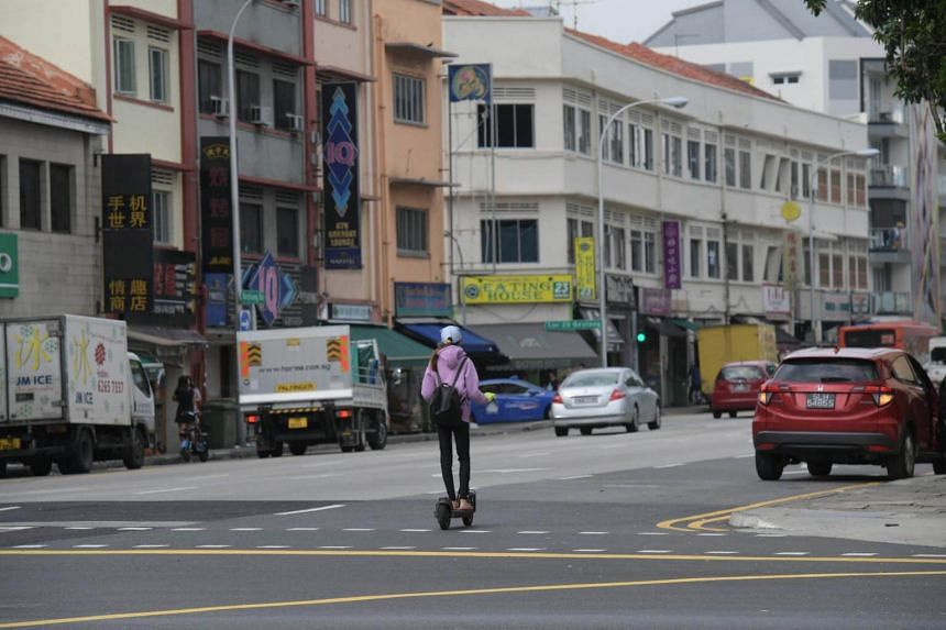 A personal mobility device user seen travelling alongside cars, vans and pickups in Geylang on Jan 3, 2018.
