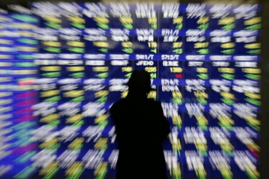 A man looks at at an electronic stock quotation board outside a brokerage in Tokyo.
