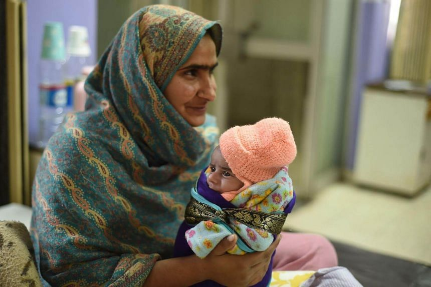 Sartaj holding her 15-day-old daughter Kinza, who is suffering from diarrhoea and a blood infection after drinking contaminated water.