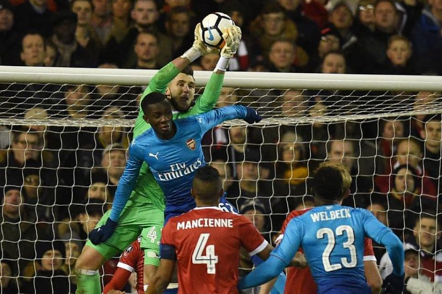 Nottingham Forest's English goalkeper Jordan Smith (left) makes a save during the English FA Cup third round football match between Nottingham Forest and Arsenal at The City Ground in Nottingham, central England, on Jan 7, 2018.