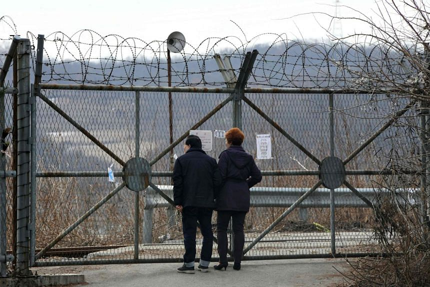 A couple stands in front of a military fence at the Imjingak peace park near the Demilitarized Zone DMZ dividing the two Koreas at the border city of Paju on Jan 8, 2018.