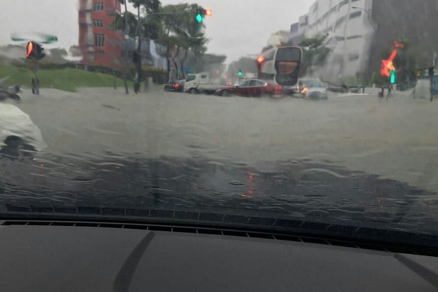 A photo taken from a dashboard camera of a vehicle, showing the flooded roads at Upper Changi Road and Bedok North Avenue 4.