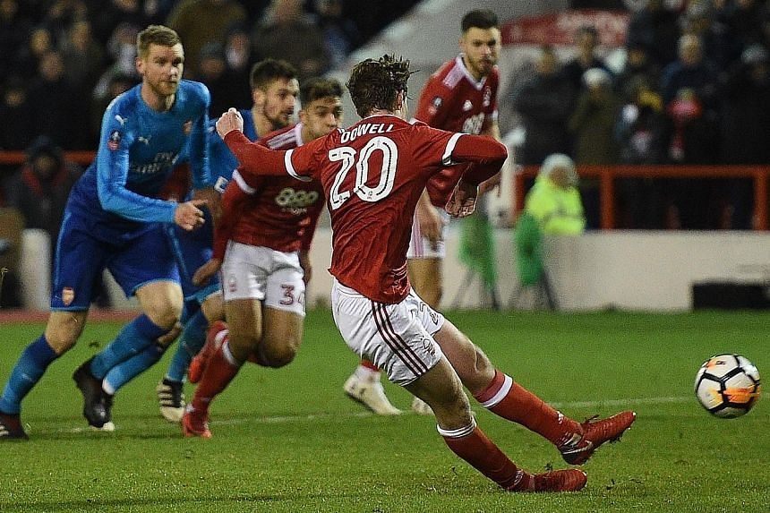 Striker Ben Brereton (far left, with Matty Cash) celebrating his 64th-minute penalty against Arsenal that made it 3-1 to hosts Nottingham Forest in the English FA Cup third round. Below: Kieran Dowell's late penalty, which he accidentally kicked twic
