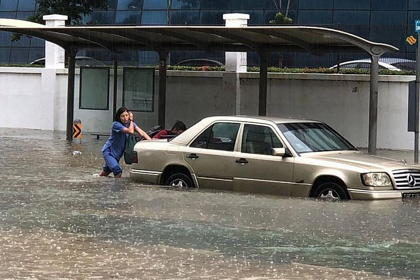 A car stranded along Upper Changi Road yesterday, one of nine areas in the east hit by flash floods. Drainage works taking place in eight of the affected areas are expected to be completed by March next year.