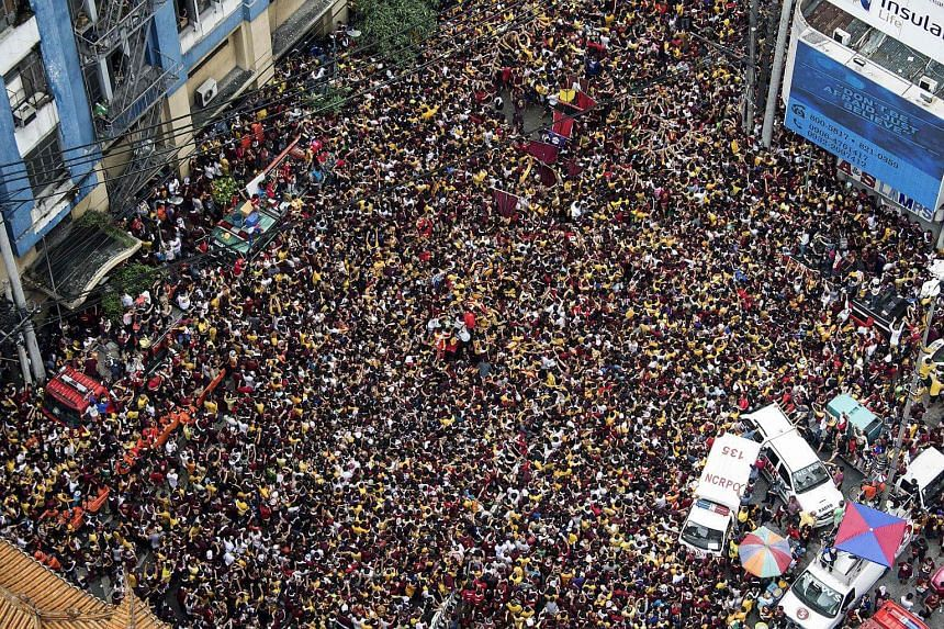 Devotees carry the statue of the Black Nazarene to the carriage at the start of the annual religious procession in Manila, on Jan 9, 2018.