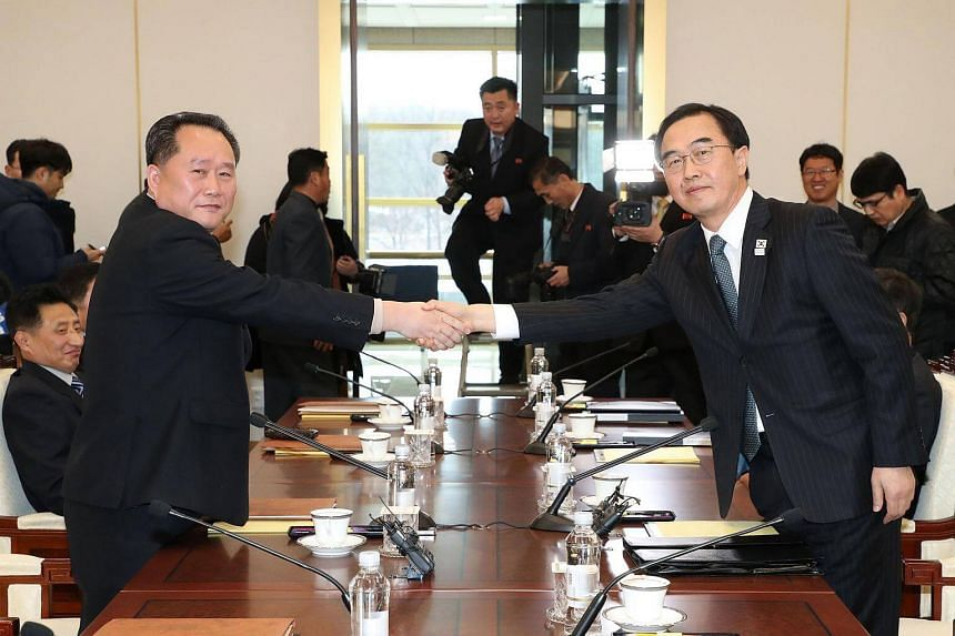 South Korea Unification Minister Cho Myung Gyun (right) shakes hands with North Korean chief delegate Ri Son Gwon during their meeting.