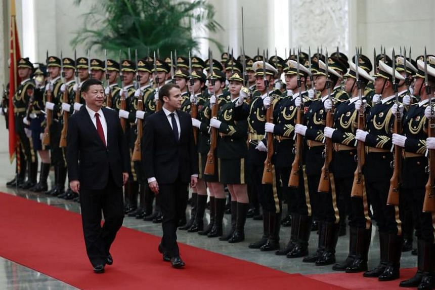 French President Emmanuel Macron (centre) and his Chinese counterpart Xi Jinping (left) review honour guards during a welcome ceremony at the Great Hall of the People in Beijing on Jan 9, 2018.