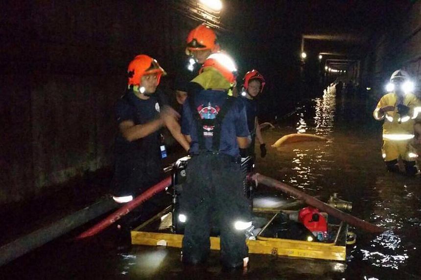 SCDF personnel working to clear water in the flooded MRT tunnel near Bishan station, on Oct 8, 2017.