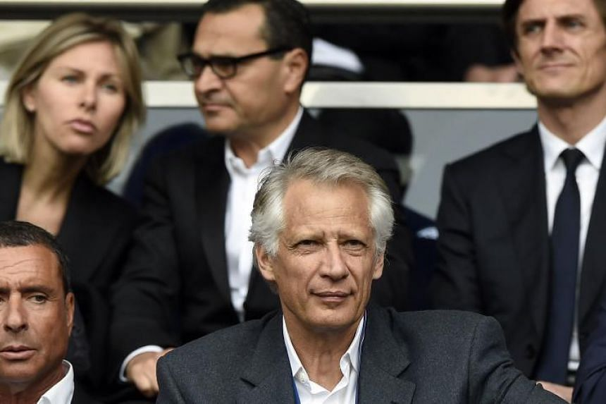 This file photo taken on April 23, 2014 shows France's former Prime Minister Dominique de Villepin (centre) and businessman Alexandre Djouhri (left) attending the French L1 football match between Paris Saint-Germain (PSG) and Evian-Thonon (ETG) at th