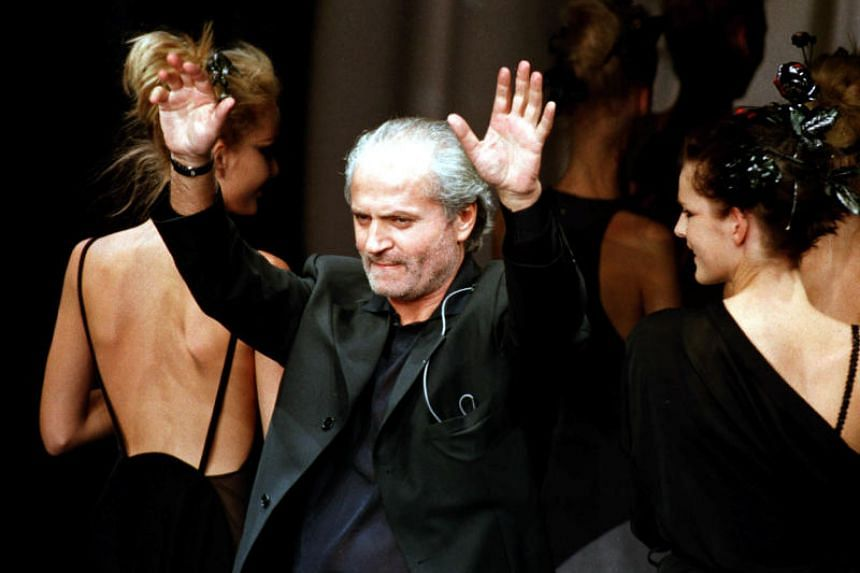 Italian designer Gianni Versace waves at the end of his presentation of his spring-summer '97 ready-to-wear collection at a Milan fashion show, Oct 5, 1996.