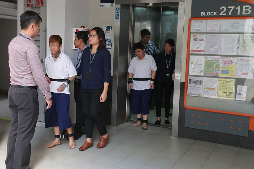 Raslindawati Abdul Rashid and Joanna Michell Tan Jiamei (back) were taken back to the crime scene at Block 271B in Sengkang Central where they had allegedly set fire to a Housing Board unit.
