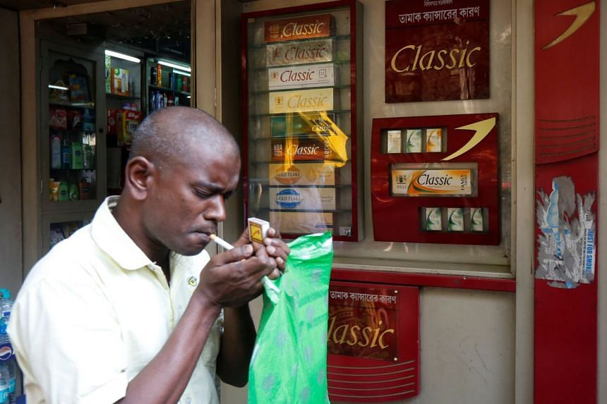 A man lighting a cigarette in front of a departmental store in Kolkata, India.