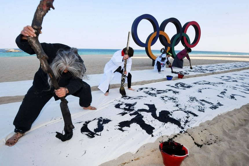 A calligraphy performance is staged in front of the Olympic rings on a beach on Gangneung, South Korea.