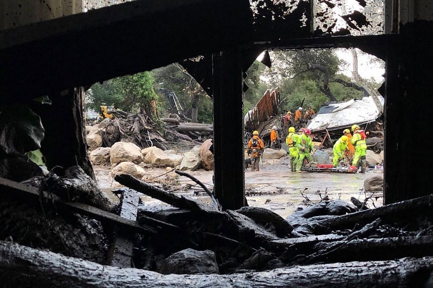 Firefighters work amid flood waters and debris flow during heavy rains in Montecito, California.