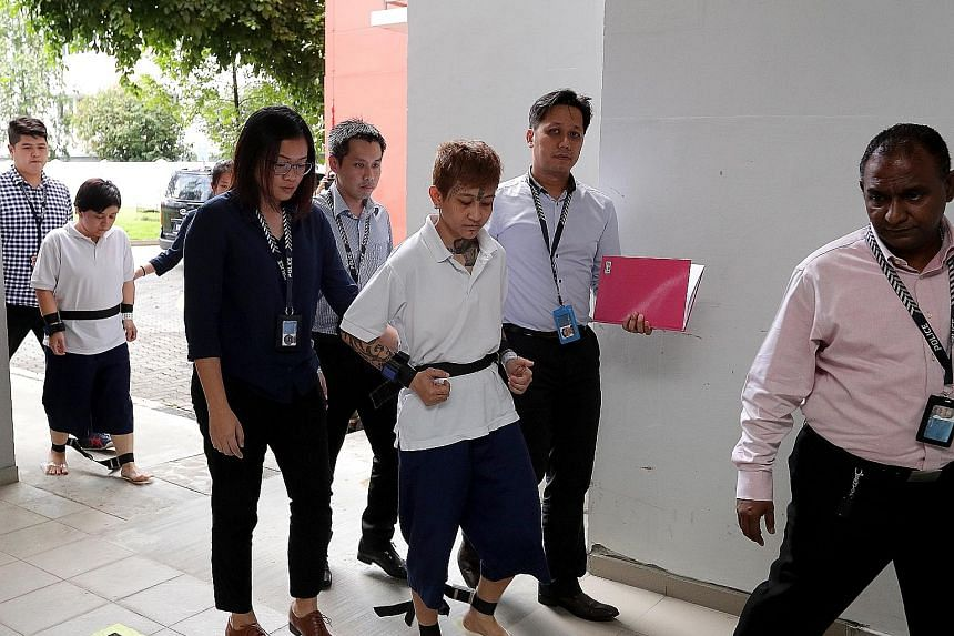 Raslindawati Abdul Rashid (centre) and Joanna Michell Tan Jiamei with police officers at the crime scene at Block 271B in Sengkang Central yesterday. The two women are suspected of setting fire to the entrance of a flat in the block.