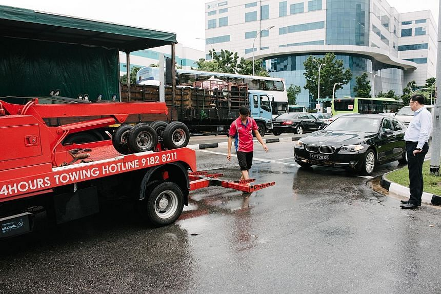 "Mr Ricky Ng (right) waiting for his BMW car to be towed after he was caught in Monday's flood near the junction of Upper Changi Road and Bedok North Avenue 4. ""The damage is quite bad as water got into the engine, exhaust and air intake system,"" he s"