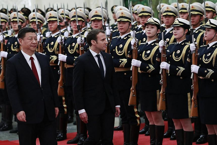 French President Emmanuel Macron and China's President Xi Jinping at a welcome ceremony with honour guards in Beijing yesterday.