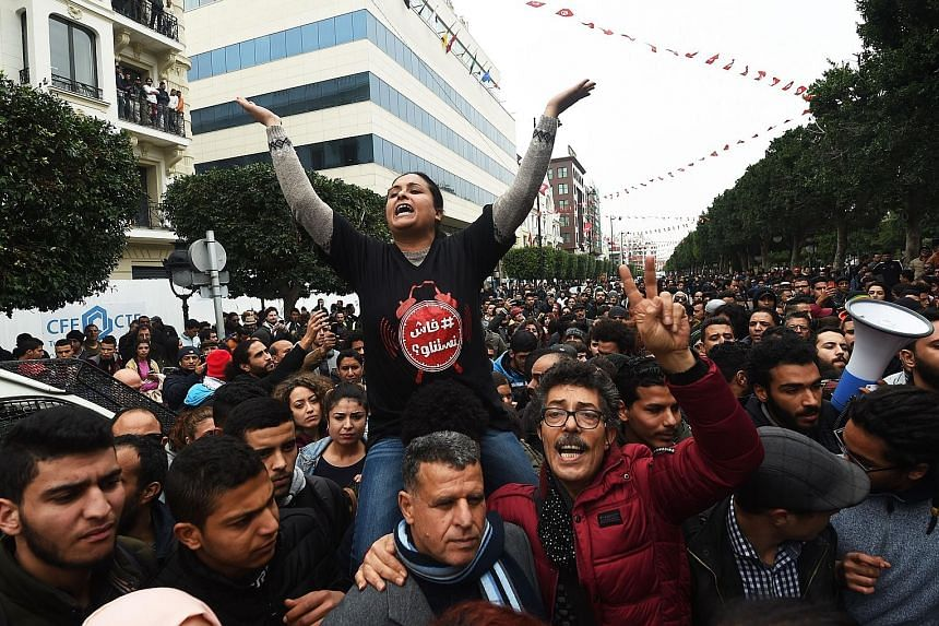 Tunisians demonstrating against the government and price hikes yesterday. Protests hit several parts of Tunisia where dozens of people were arrested and one man died in unclear circumstances amid anger over rising prices, the authorities said.
