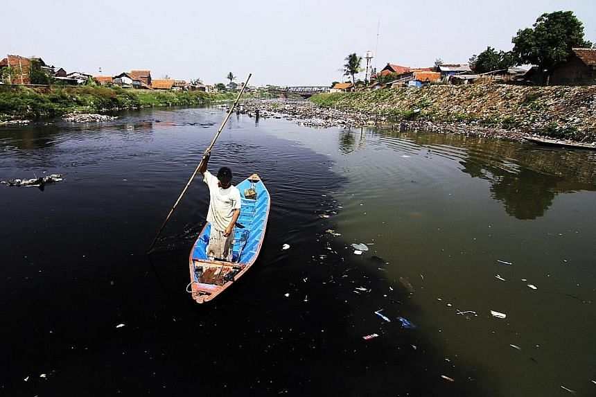 A resident collecting plastic and other recyclables on the Citarum River, located 70km east of Jakarta, whose water has partially turned black because of chemical waste and dyes discharged from factories operating along its banks. Wet markets and ani