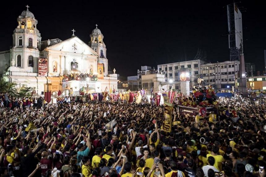 Catholic devotees jostle to try to touch the life-size statue of the Black Nazarene as it arrives at the Quiapo Church during the annual procession in Manila on Jan 10, 2018.