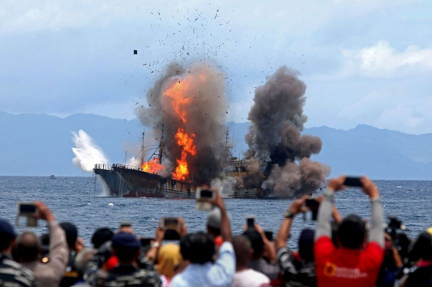 People taking pictures of a ship being blown up blown up by the Indonesian government, after it was found fishing illegally, at Morela village in Ambon island on April 1, 2017.