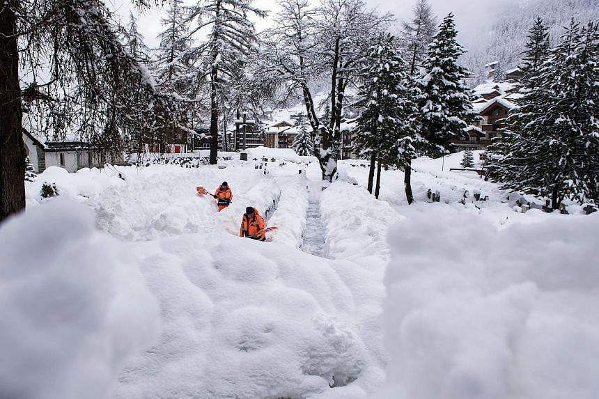Workers clearing snow from a path in Zermatt, after heavy snowfall in the region, on Jan 9.