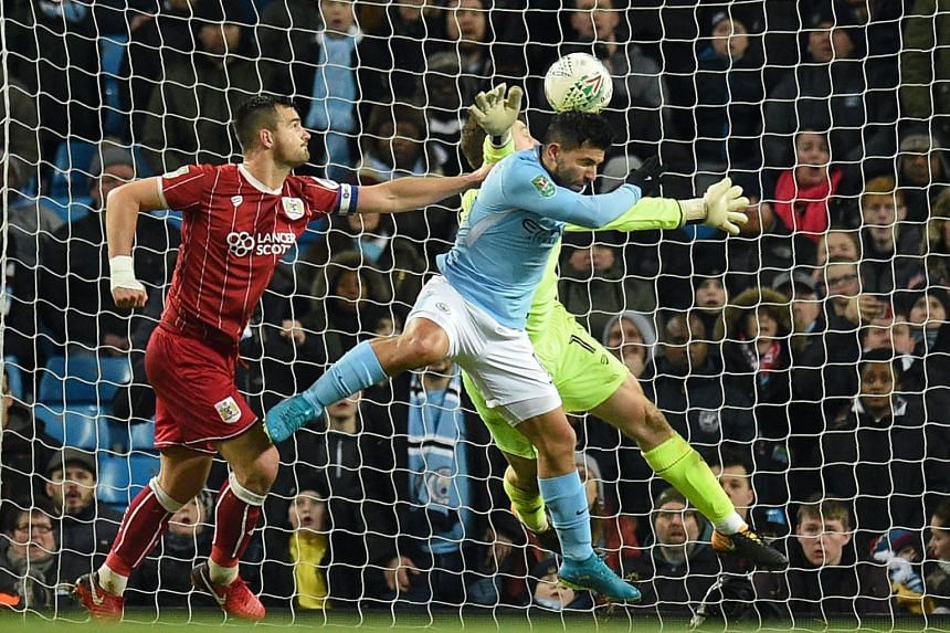 Aguero (centre) jumps to score City's late winning goal.