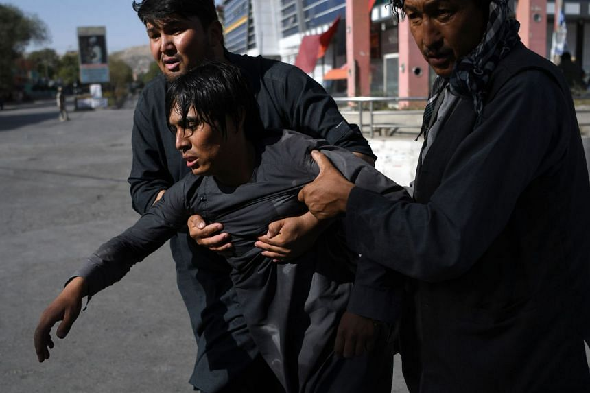 Men help carry a wounded friend near the site of a suicide attack claimed by ISIS targeting a Shi'ite mosque in Kabul, on Aug 25, 2017.