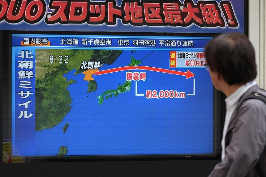 A pedestrian looks at a TV screen displaying a map of Japan and the Korean Peninsula on Sept 15, 2017, following a North Korean missile test that passed over Japan.