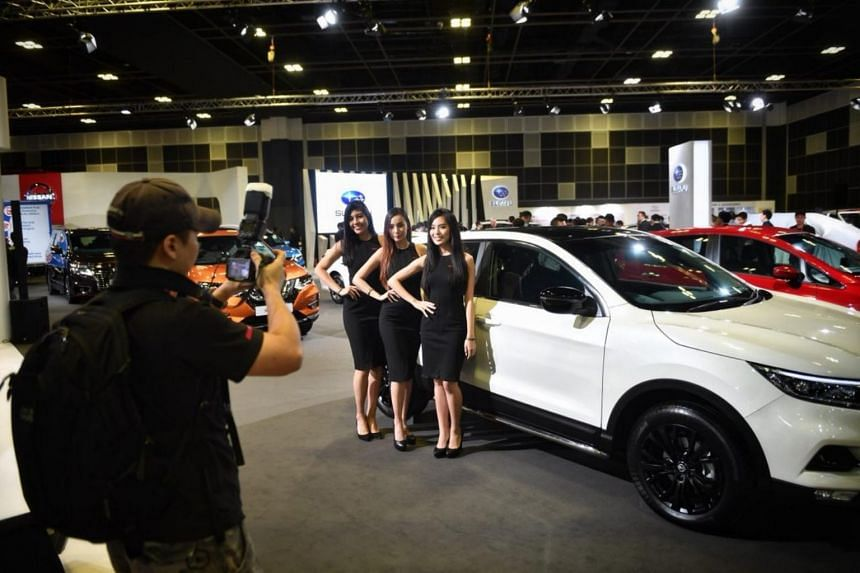 Models posing for photos at the Singapore Motorshow.