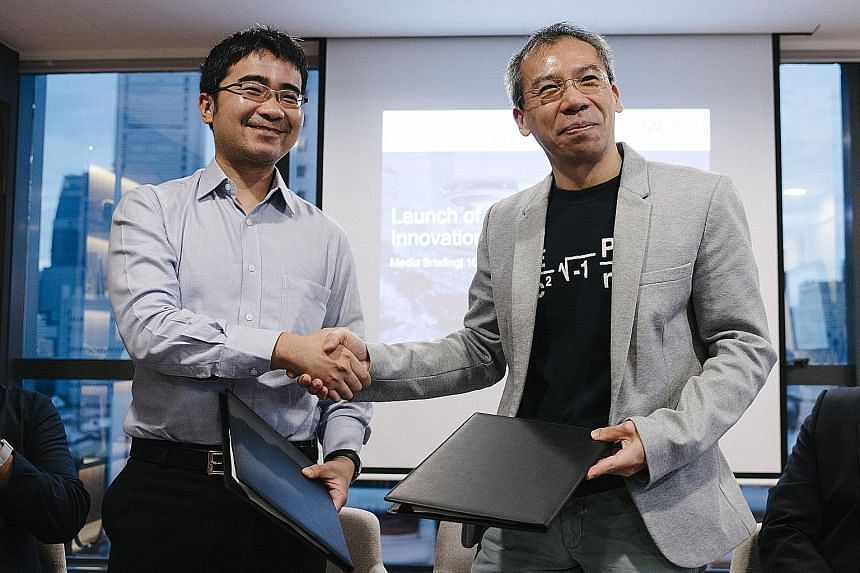 SMU law school dean Goh Yihan (far left) and SAL chief operating officer and chief financial officer Paul Neo at the signing of the memorandum of understanding yesterday.