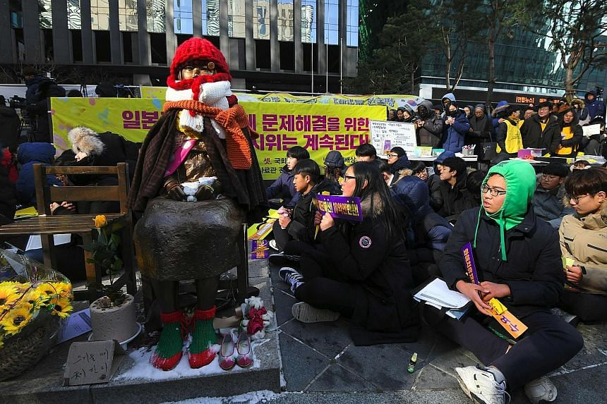Protesters beside a comfort woman statue at a rally near the Japanese Embassy in Seoul yesterday. In his national address, South Korean President Moon Jae In said the 2015 comfort women accord with Japan was undeniable, but the issue can be resolved