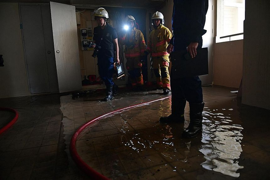 SCDF officers leaving the affected flat on the 15th floor after the blaze was put out in 15 minutes of their arrival.