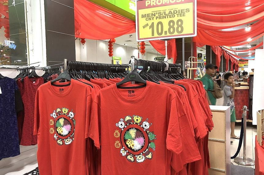 The cotton T-shirt sold by Giant Hypermarket in Malaysia shows 10 of the 12 animals of the zodiac around a platter of yu sheng. The dog and pig were represented by Chinese characters instead.