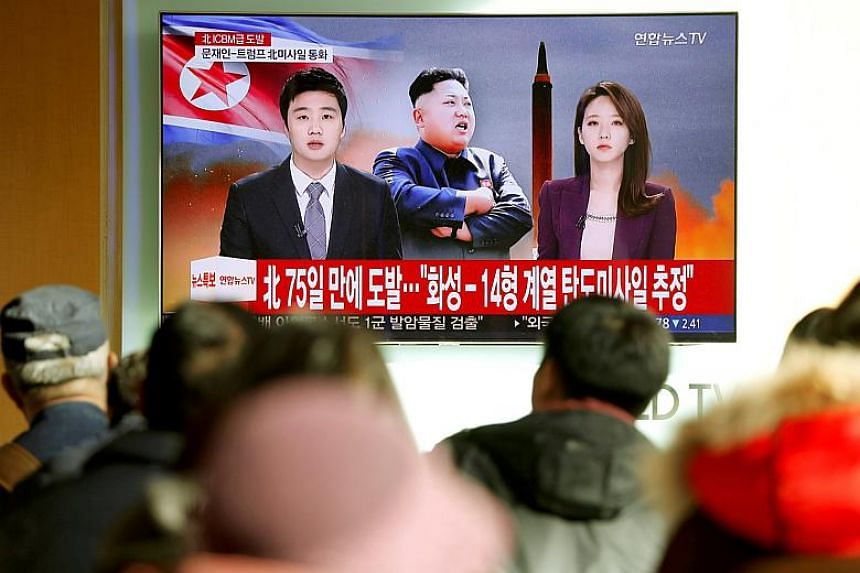 People watch a TV broadcasting a news report on North Korea firing what appeared to be an intercontinental ballistic missile that landed close to Japan, in Seoul on Nov 29, 2017.