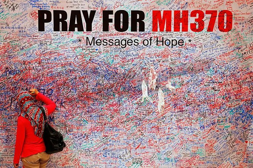 A woman leaves a message of support and hope for the passengers of the missing Malaysia Airlines MH370 in central Kuala Lumpur on Mar 16, 2014.