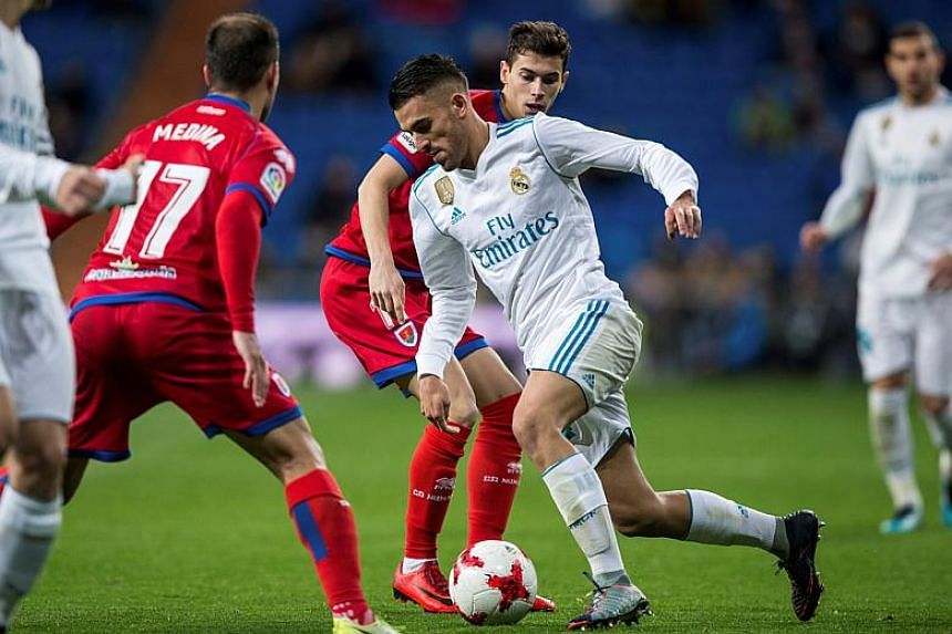 Real Madrid's midfielder Dani Ceballos (right) tries to escape between Numancia's Saul Garcia and Unai Medina during their Spanish King's Cup round of 16 second leg soccer match played at Santiago Bernabeu stadium in Madrid on Jan 10, 2018.