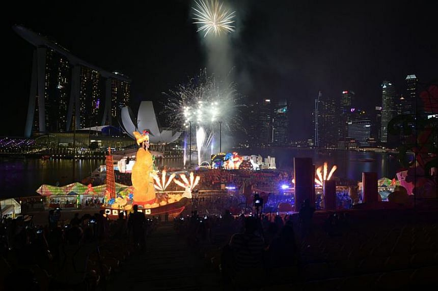 The God of Fortune holding court as fireworks lit up the night sky on the first day of the River Hongbao carnival at The Float @ Marina Bay on Jan 26, 2017.