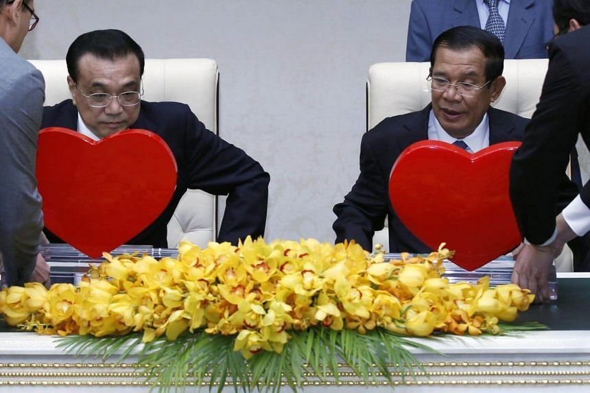 Cambodian officials hand over hearts to Chinese Prime Minister Li Keqiang and Cambodian Prime Minister Hun Sen during a signing ceremony at the Peace Palace in Phnom Penh on Jan 11, 2018.